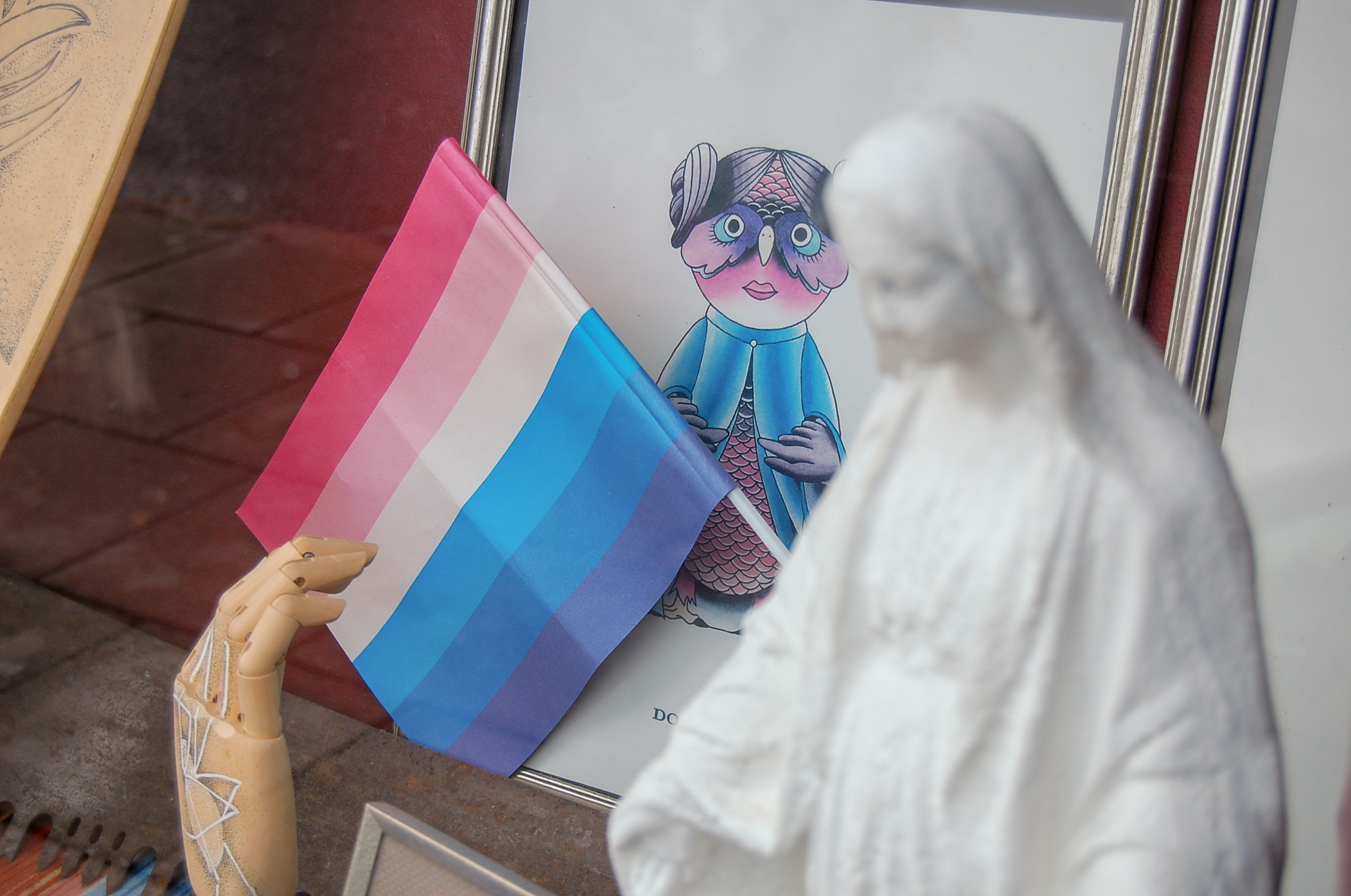 En solblekt regnbågsflagga i fönstret hos Grindhouse tattoo. Foto: Nina Kartal