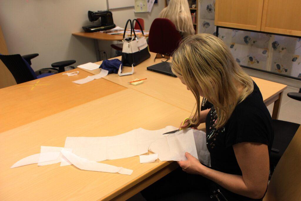 Buffy Lindwall klipper ut ett mönster till en halloweenklänning hon ska sy. Hon berättar att det är svårt att ta initiativ när man mår dåligt och att det är viktigt att få möjlighet att bryta isoleringen.
