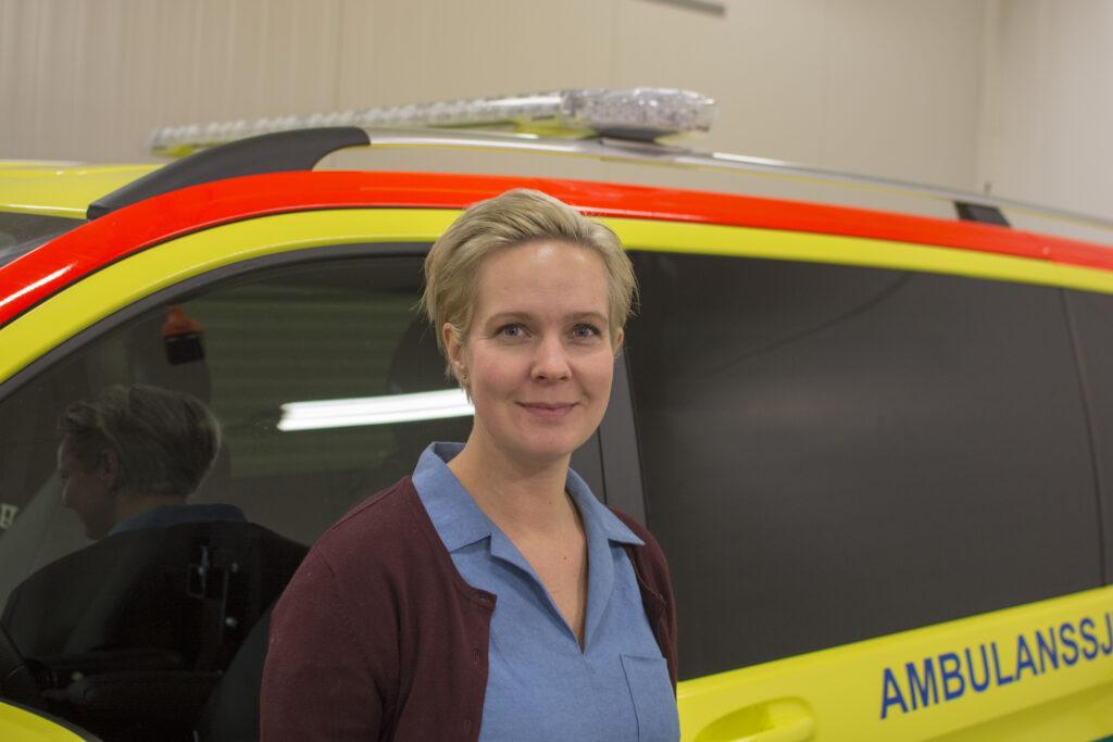 Sandra Önnheim är projektledare för Prehospital Akut Psykiatri, Psykiatriambulansen i bakgrunden. Foto: Region Skåne