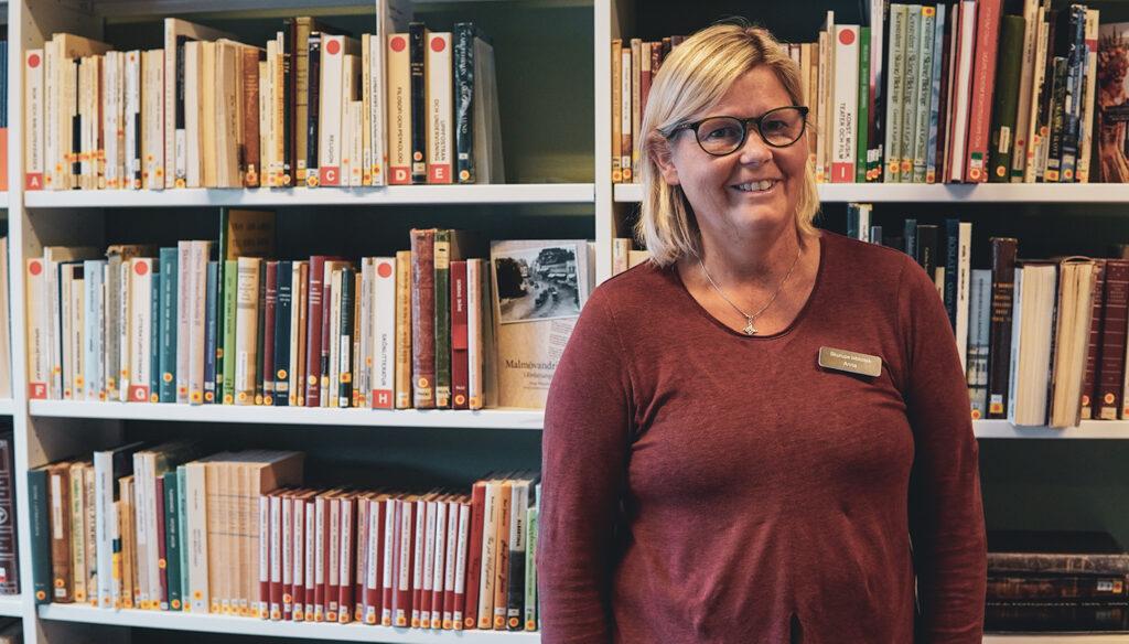 """Bibliotekarien Anna Gustafsson framför """"skånehyllan"""" där släktforskningsintresserade besökare snart ska ses igen efter ett och ett halvt års pandemiuppehåll."""